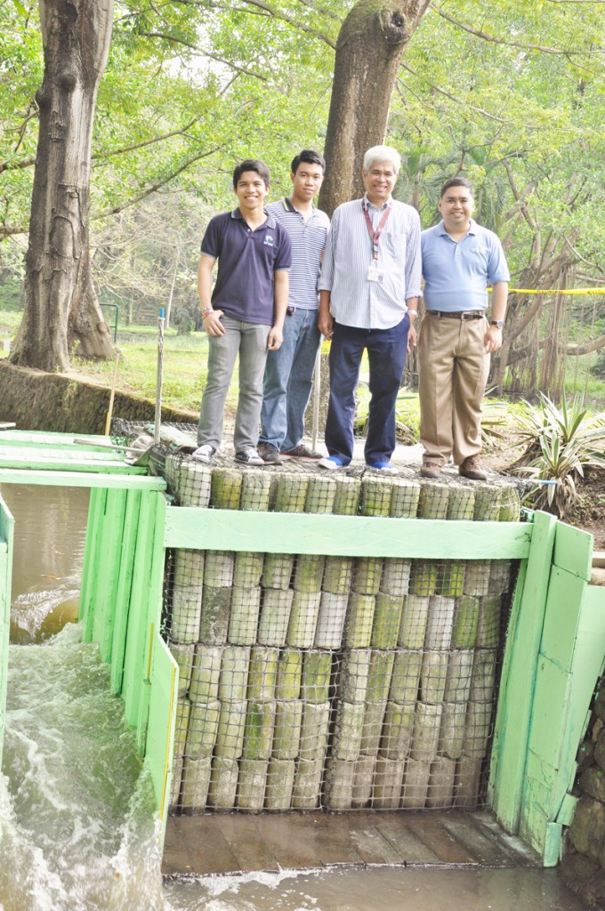 Inventors Kent Renier Carandang and Rhey Joseph Daway, with their advisers Dr. Leonardo Liongson and Dr. Mark Albert Zarco, with the Gaia Dam prototype built at the UP Diliman Lagoon. Photo courtesy of Kent Carandang and Rhey Daway.